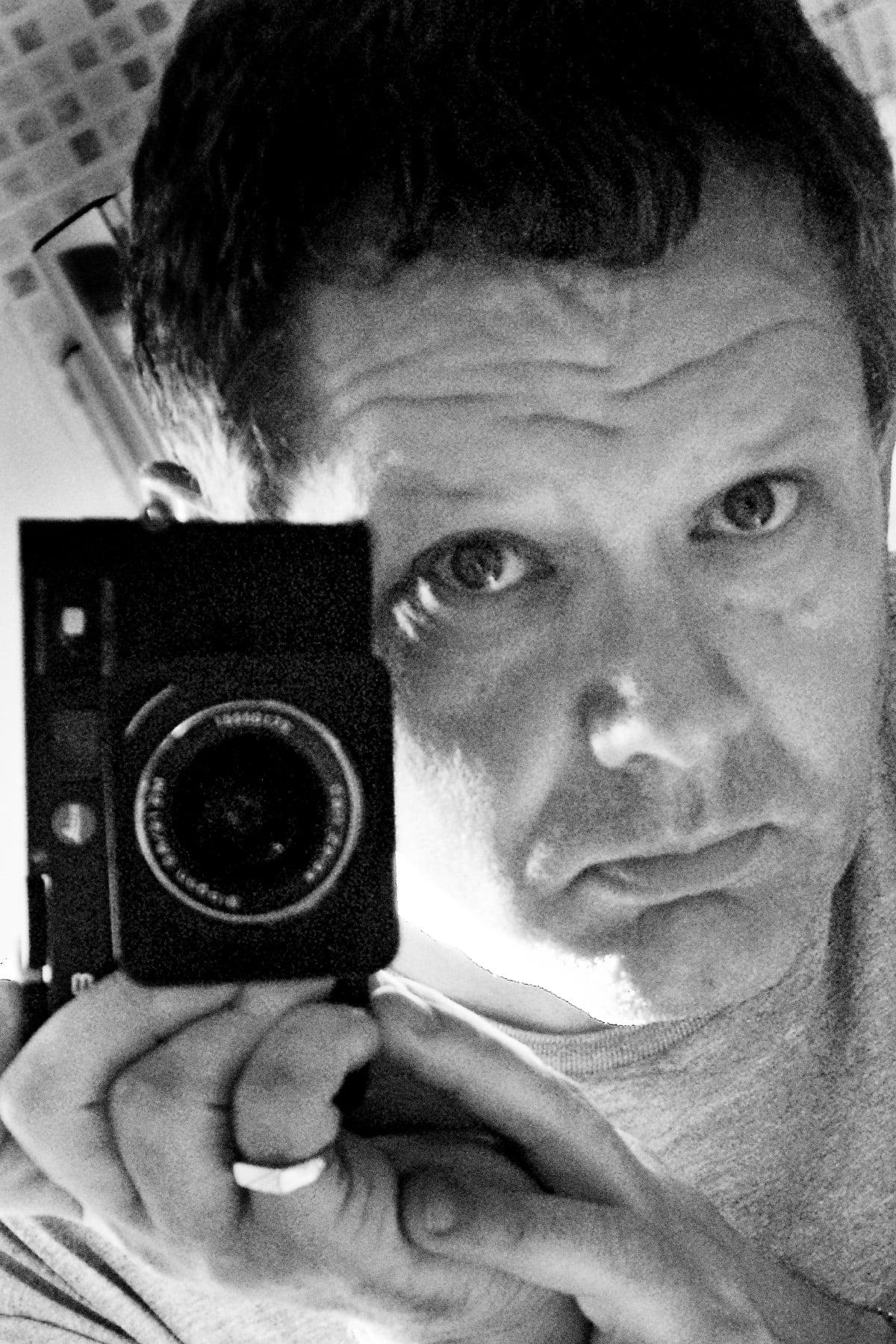 black and white headshot holding camera