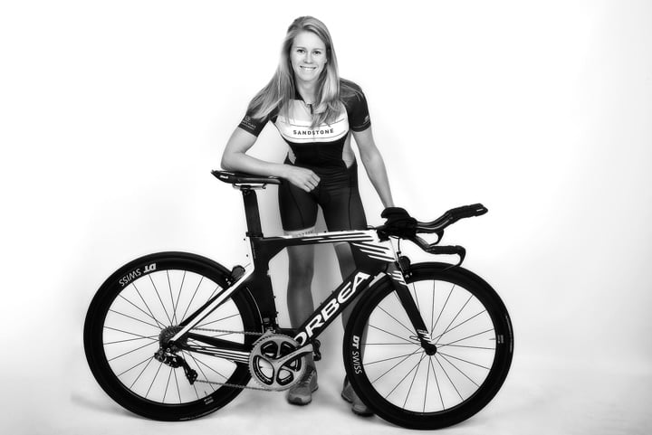 Triathlete lady with racing bike in the studio