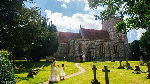 bride and bridesmaid walking up sunny path into church