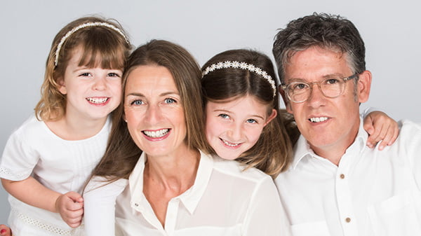 family of 4 at a studio photoshoot smiling and wearing white