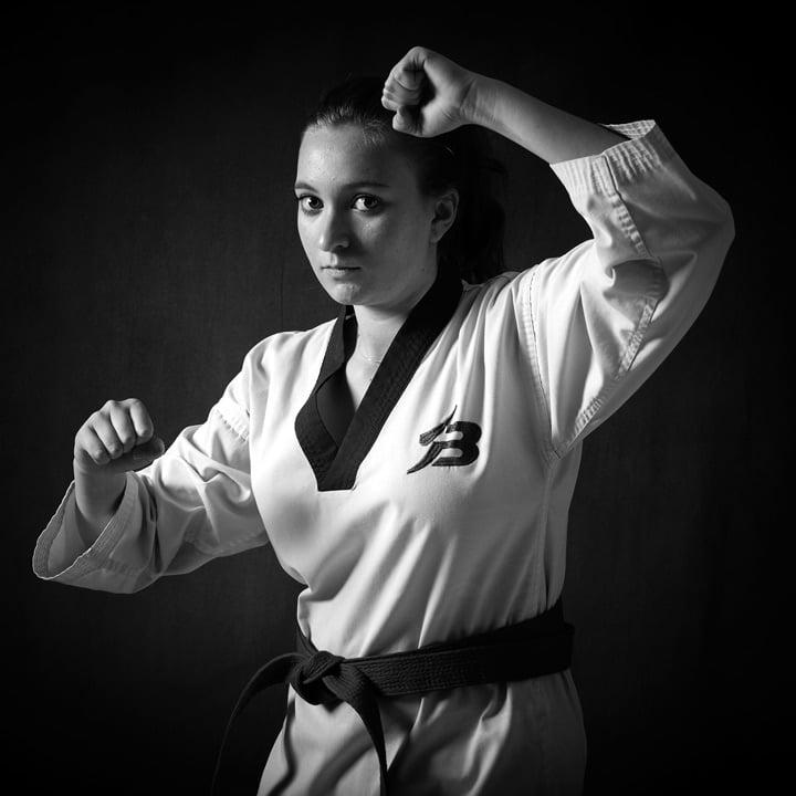 fierce looking girl in karate gear against black background