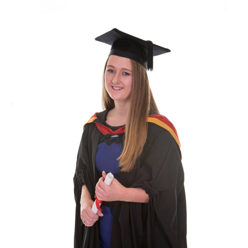 graduate with moarterboard, gown and holding certificate in studio session
