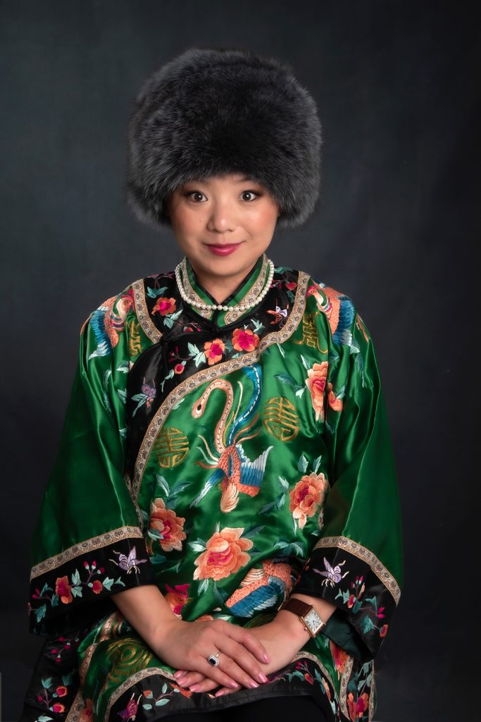 chinese business woman in traditional chinese outfit wearing a fur hat